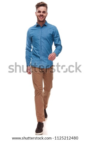 happy casual man with blue shirt walking forward on white background ,full length picture #1125212480