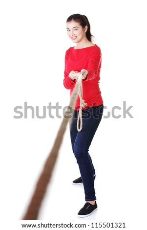 Happy casual woman pulling a rope, isolated on white