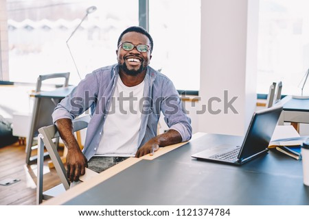 Happy casually dressed dark skinned male laughing sitting at desktop enjoying working process, cheerful african american hipster guy satisfied with online business spending time in coworking space #1121374784