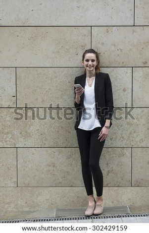 Happy Caucasian Businesswoman using her smart phone.  Business woman standing outside in modern city.