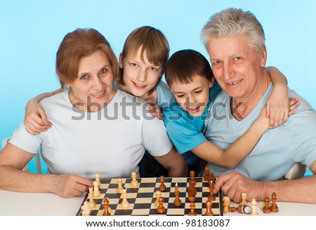 Happy Caucasian campaign of playing chess against a light background
