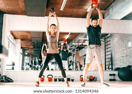 Happy Caucasian couple doing strength exercises with kettlebell while standing in gym. In background mirror with their reflection. #1314094346