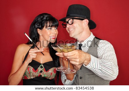 Happy Caucasian couple enjoy martini and cigarette over maroon background