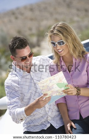 Happy Caucasian couple looking at map - stock photo