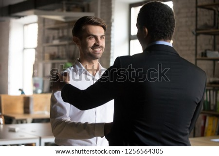 Happy caucasian employee getting rewarded promoted hired feeling proud shaking hand of black manager congratulating with good work, successful worker handshaking satisfied boss, employee recognition