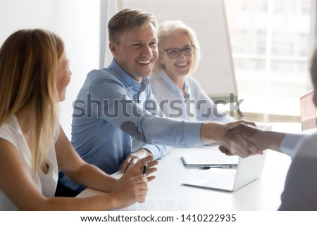 Happy caucasian employer hr handshake employ successful african candidate made good first impression at job interview, smiling manager shake hand make service business deal with client hiring concept