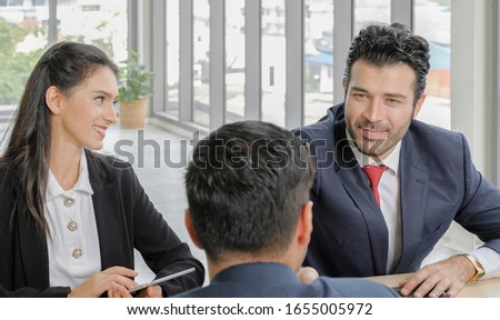 Happy caucasian executive manager and secretary are smiling and making handshake with business partner in office meeting room.