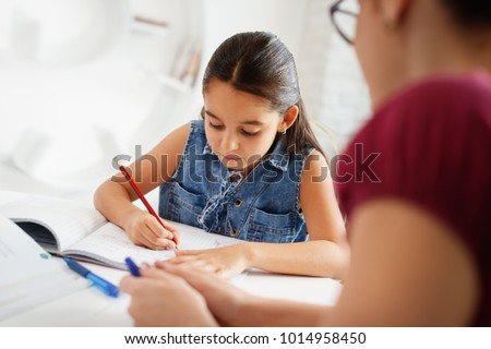 Happy caucasian family at home. Hispanic mother and female child. Latina mom helping daughter with school homework. Education, people, motherhood and relationship, woman teaching and girl learning #1014958450