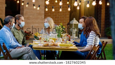 Happy Caucasian family in medical masks sitting at table with meal outdoor at picnic and talking. Joyful young and old people having dinner and having nice communication. Pandemic corona concept.