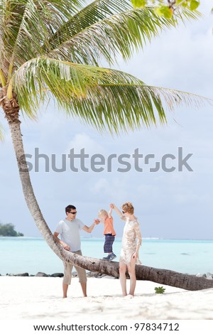 happy caucasian family with toddler enjoying beach vacation