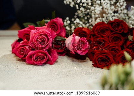Happy caucasian florist making bouquets of red and pink roses for valentine's day. Concept of human emotions, facial expression, love, and hard work in this pandemic times. Photo stock ©