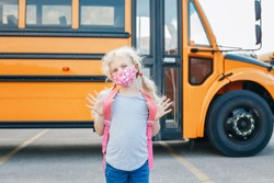 Happy Caucasian girl student wearing face mask near yellow bus. Kid with personal protective equipment on face. Education and back to school in September. New normal during coronavirus.