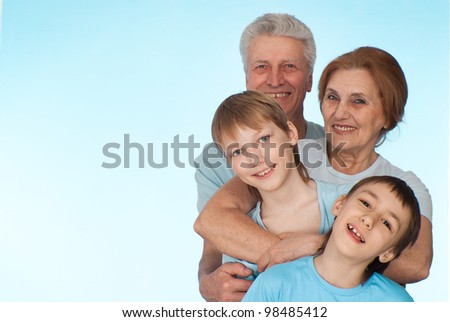 Happy Caucasian grandparents with grandchildren fooled on a light background - stock photo