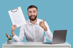 Happy Caucasian guy holding resume and showing thumb up gesture at his desk, blue studio background. HR manager finding perfect worker for business team. Successful employment and headhunting concept