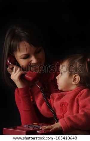 Happy Caucasian happy mother and daughter talk on the phone on a dark background