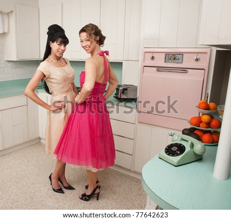 Happy Caucasian housewives in a retro kitchen with hand on hips