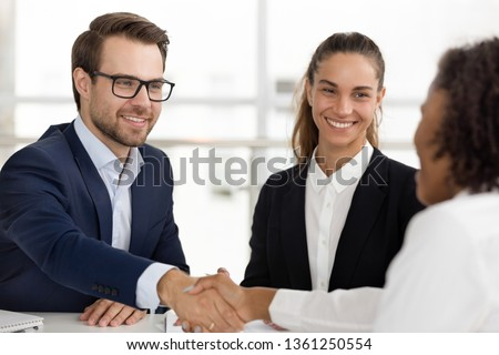 Happy caucasian hr handshaking hiring successful african job candidate at business interview, smiling manager shake hand employ client make services deal good first impression, human resource concept