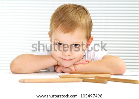 Happy Caucasian male sitting at the table draws on a light background