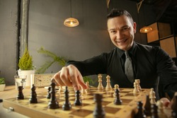 Happy Caucasian man chess player sitting at home and playing chess.