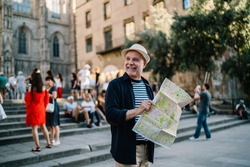 Happy Caucasian man 60s enjoying solo trip vacations for exploring Italy during retirement, cheerful male tourist in straw hat using paper orientation map for walking around historis center
