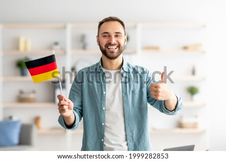 Happy Caucasian man showing thumb up and flag of Germany, posing and smiling at camera indoors. Cheerful millennial student recommending foreign education, learning German language Foto stock ©