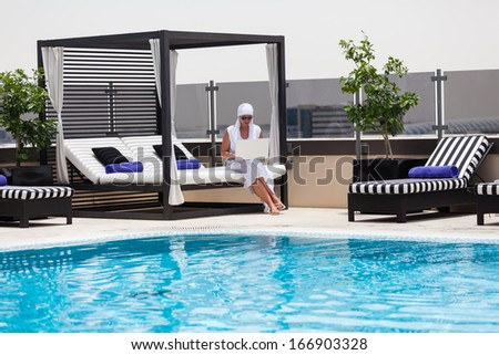 Happy Caucasian mid age woman enjoying a relaxing afternoon near to swimming pool and using a laptop
