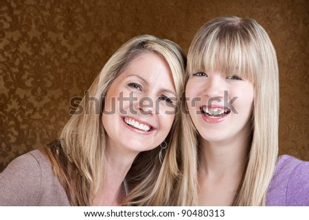 Happy Caucasian mom and daughter smile over green background