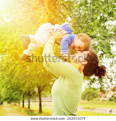 Happy Caucasian mother and son outdoors in park on sunny spring day. Young brunette mother lifting her son in park having fun enjoying motherhood. Square, retouched.