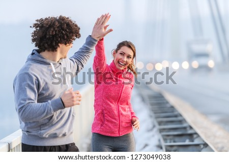 Happy Caucasian runners giving high five during running on the bridge on cold weather. Snow all around, wintertime.