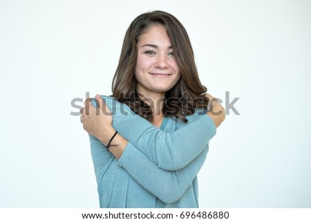 Happy caucasian woman hugging herself with natural emotional enjoying face.