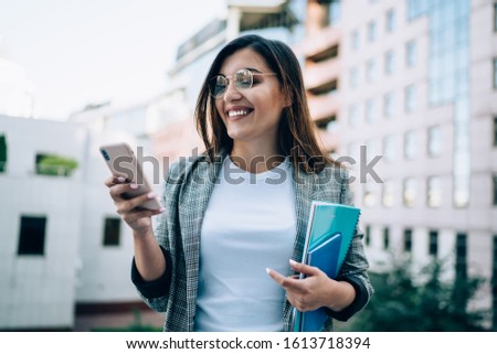 Happy caucasian woman in trendy eyewear for vision correction laughing at income message on mobile phone standing on urban settings, cheerful girl millenial enjoying discount messages on cellular