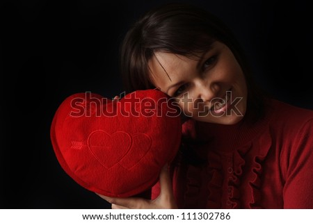 Happy Caucasian woman with a happy heart pillow on a dark background