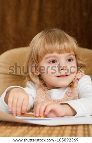 Happy Caucasian young baby draws a table on a brown background