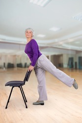 Happy charming beautiful elderly woman is doing exercise on a chair. Exercising gymnastics for health in the fitness room. Sports training.