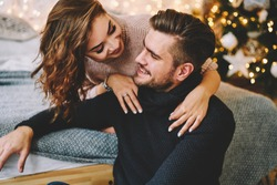 Happy charming woman dressed in knitwear talking to her handsome boyfriend spending time at cozy home, romantic couple in love happy about being together celebrating winter holidays in good mood