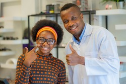 Happy cheerful African teenage girl looking for stylish glasses with qualified African-American optician in optical shop.