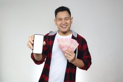 Happy cheerful Asian man holding uang Indonesian rupiah money and showing phone with empty blank screen