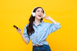 Happy cheerful Asian woman wearing wireless headphones listening to music from smartphone studio shot isolated on yellow background