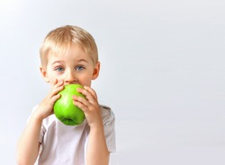 Happy cheerful boy eats the big apple, the child is the fruit green, soft focus, isolated on white background