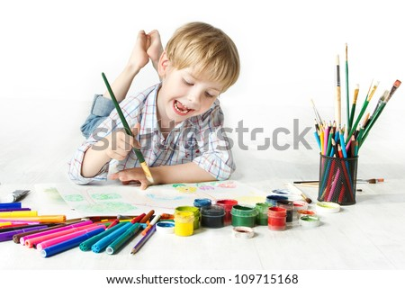 Shutterstock Happy cheerful child drawing with brush in album using a lot of painting tools. Creativity concept.