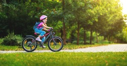 happy cheerful child girl riding a bike in Park in the nature