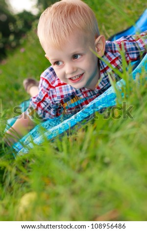 Happy cheerful child lying is among the green grass in a meadow