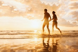 Happy cheerful couple having fun running to the sea together and doing splashes of water on a tropical beach at sunset - concept about romantic vacation, honeymoon