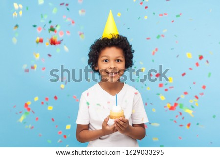 Happy cheerful cute little boy with funny party cone on head holding cupcake and smiling while confetti falling around, his look expressing pure joy and happiness. indoor studio shot blue background Foto stock ©