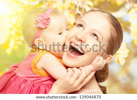 Happy cheerful family. Mother and baby kissing, laughing and hugging in nature outdoors