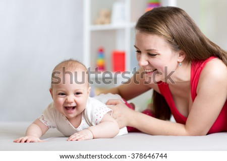 Happy cheerful family. Mother and baby playing, laughing and hugging