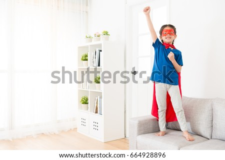 happy cheerful female children wearing superhero clothing standing on living room sofa couch and making posing ready to fly at home. #664928896