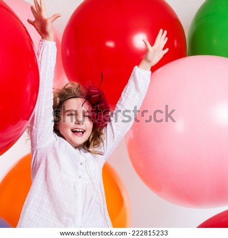 Happy cheerful girl on a background of the larger balls. Holiday. square photo