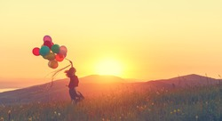 Happy cheerful girl with balloons running across meadow at sunset on nature in summer