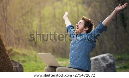 Happy cheerful hipster man with a laptop sitting outdoors in nature, freedom and happiness concept